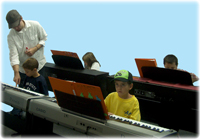 Students learning piano in a group.